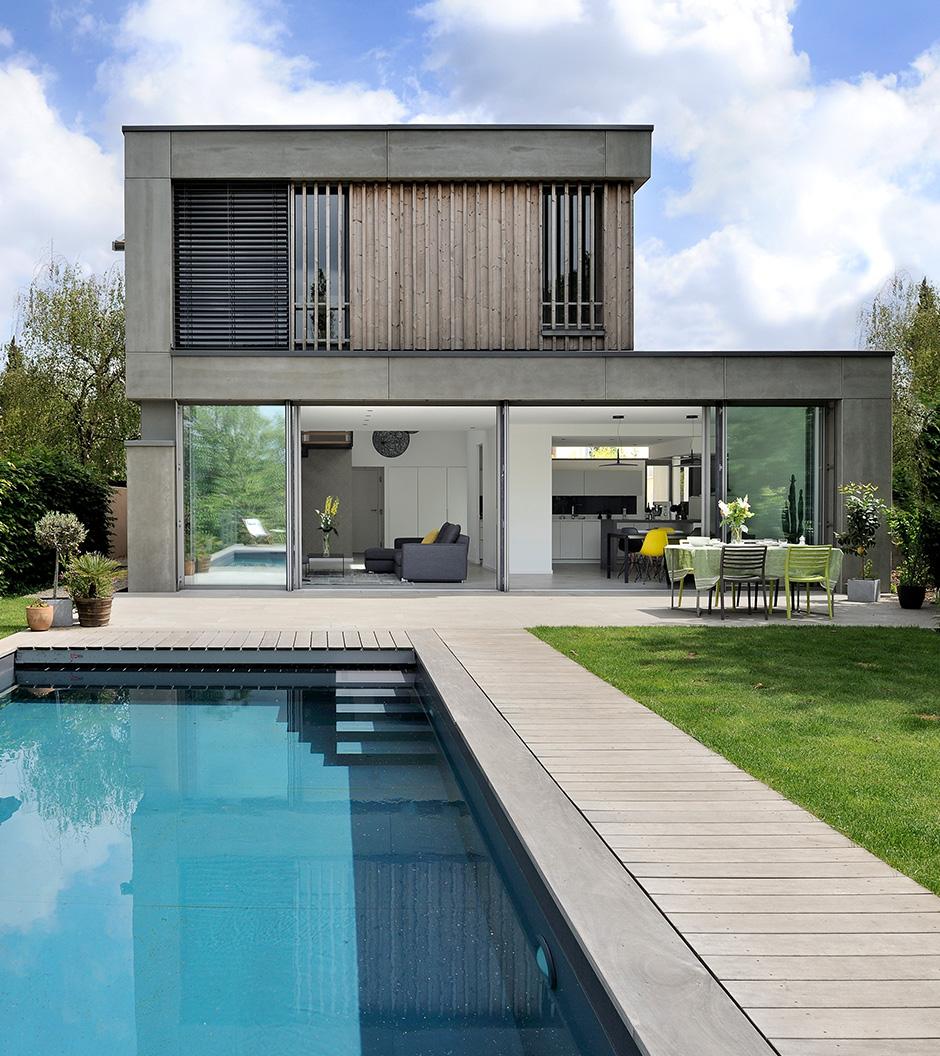 maison contemporaine en ossature bois a caluire et cuire. L'extension a des grandes baies vitrées qui s'ouvrent vers la piscine et le jardin.