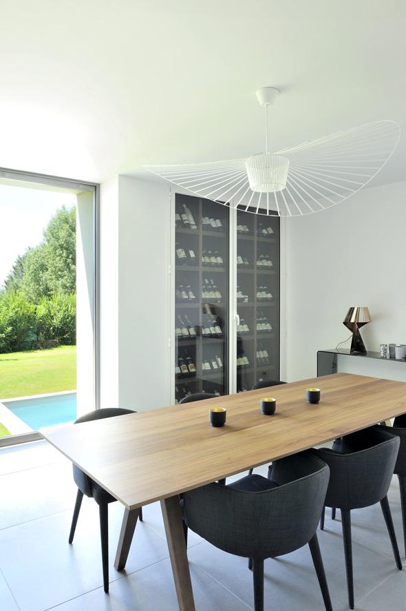 Maison contemporaine dans l'ouest de Lyon. Salle à manger avec table scandinave et cave à vin intégrée.