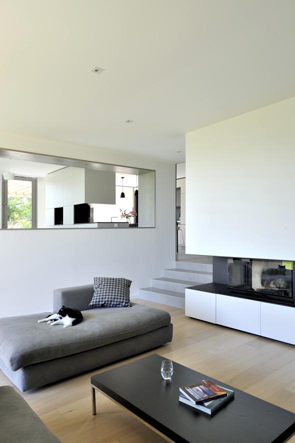 Maison contemporaine dans l'ouest de Lyon. Salon avec cheminée intégrée, escalier intérieur et vu sur la salle à manger.