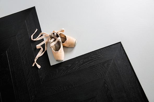 Extension contemporaine à Caluire et Cuire en ossature bois et bardage aluminium imitation zinc noir. Façade triangle, terrasse mélèze, éclairage led de la cuisine avec ilôt minimaliste. Le sol en résine vient rencontrer le parquet chevron revisité en noir.