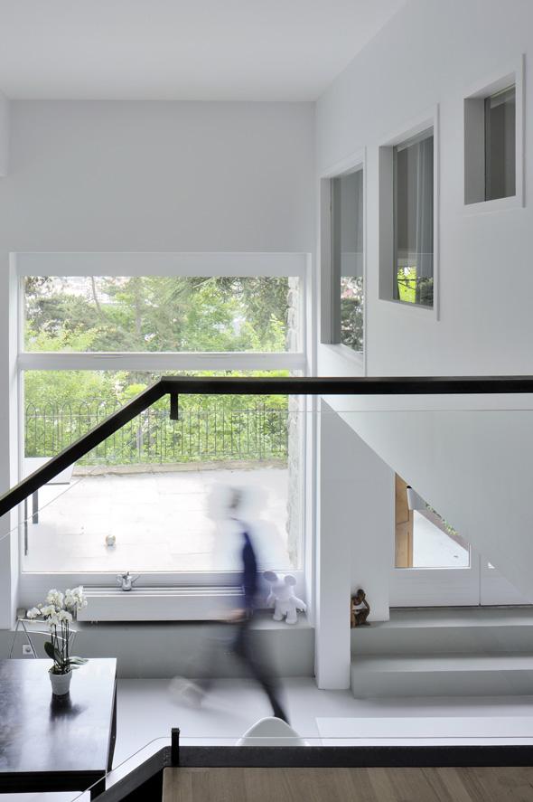 Appartement en duplex rénové de manière contemporaine et minimaliste, fenêtres intérieures.