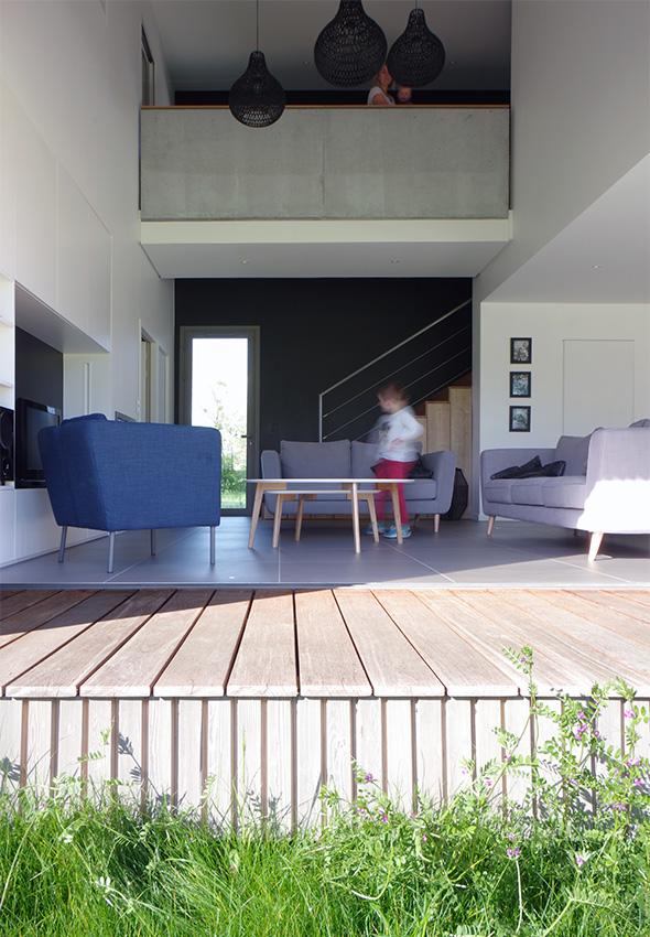 Maison contemporaine en Savoie avec un bardage bois et du béton brute. Terrasse bois et passerelle béton à l'étage.