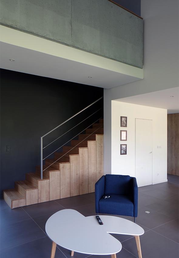 Maison contemporaine en Savoie avec un bardage bois et du béton brute. Escalier en bois et passerelle béton banché.