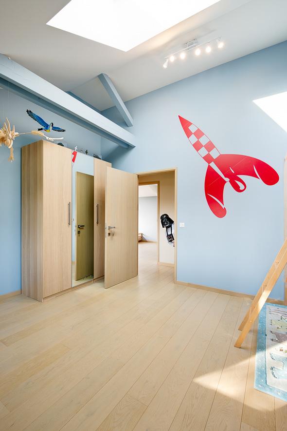 Maison à patio contemporaine sur Lyon. Chambre enfant bleu et bois avec poutres apparentes et fenêtre de toit.