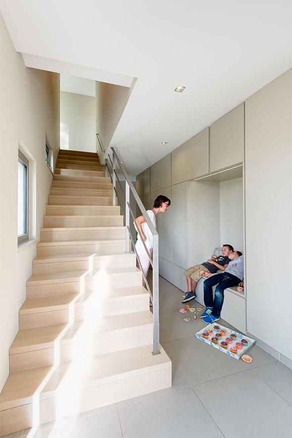 Maison à patio contemporaine sur Lyon. Entrée avec l'escalier de l'étage et un meuble de rangement sur mesure avec banc et penderie.