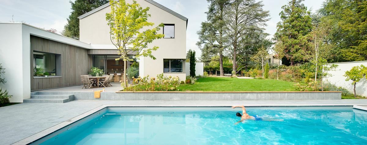Maison à patio contemporaine sur Lyon. Façade de la cuisine avec terrasse pour manger dehors et grande piscine.