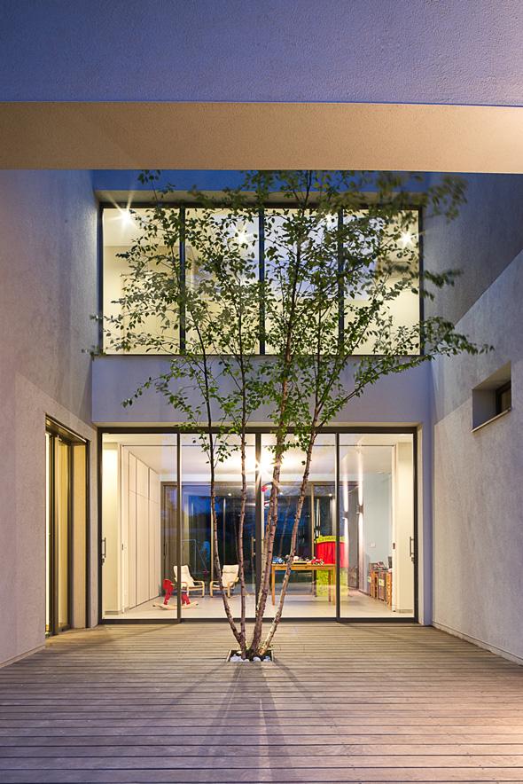 Maison à patio contemporaine sur Lyon. Patio de nuit avec éclairage de la terrasse et un arbre, transparence de la salle de jeu attenante.