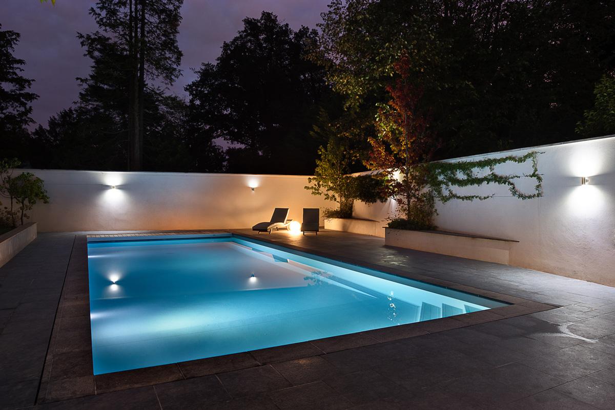 Maison à patio contemporaine sur Lyon. Piscine de nuit avec éclairage et aménagement.