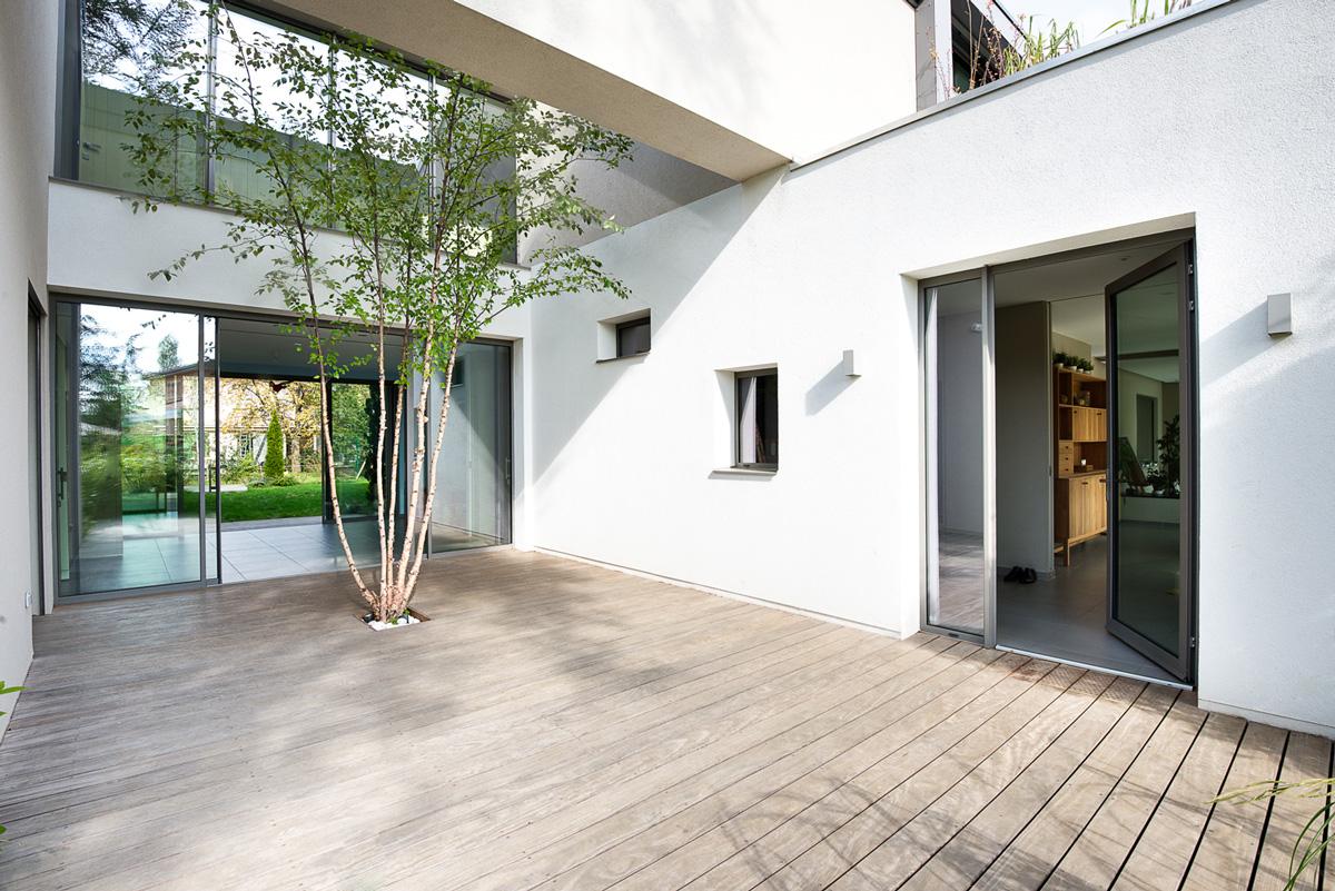 Maison à patio contemporaine sur Lyon. Patio avec terrasse, transparence de la salle de jeu et entrée