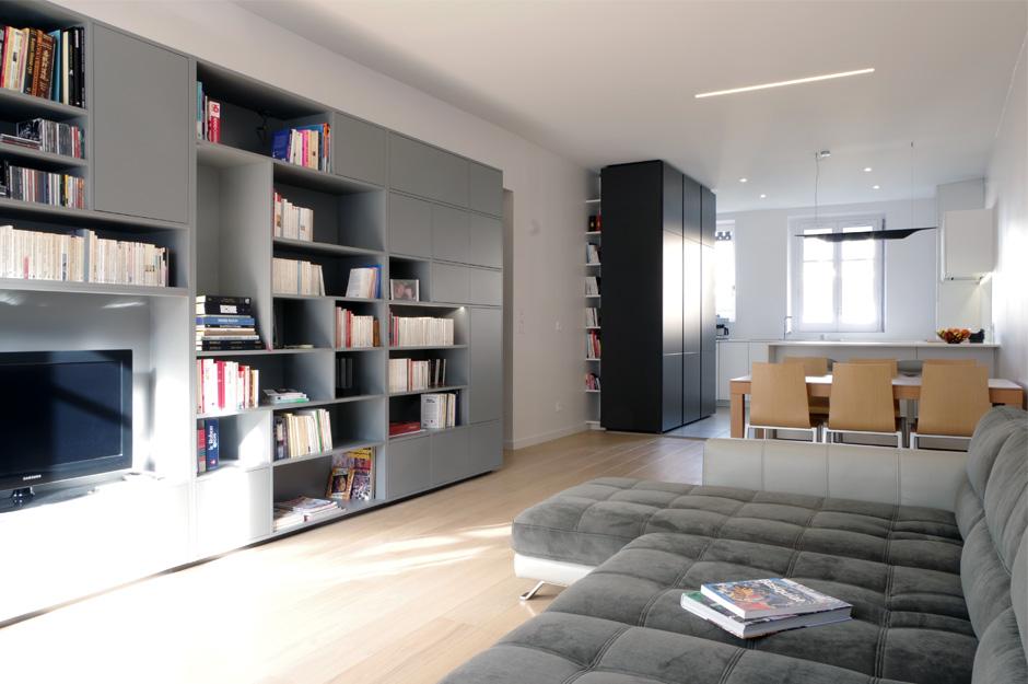 Rénovation d'un appartement contemporain à lyon avec un meuble central sur mesure. Bibliothèque dans le salon et cuisine avec un îlot.