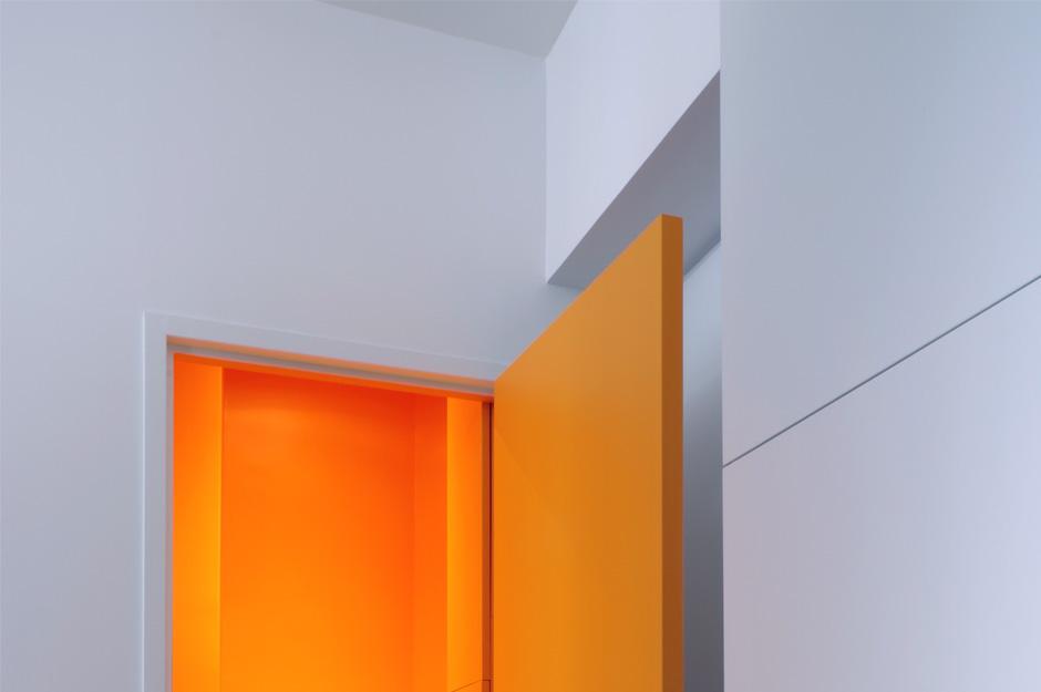 Rénovation d'un appartement contemporain à Lyon avec un meuble central sur mesure. Détail des couleurs avec le wc orange.