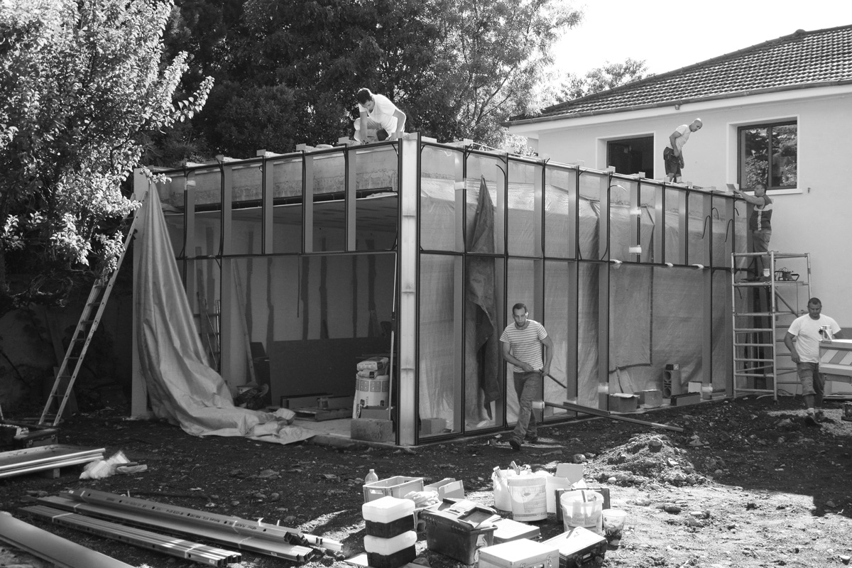 Rénovation et extension contemporaine d'une maison à Caluire de type verrière d'atelier. Chantier murs rideaux.