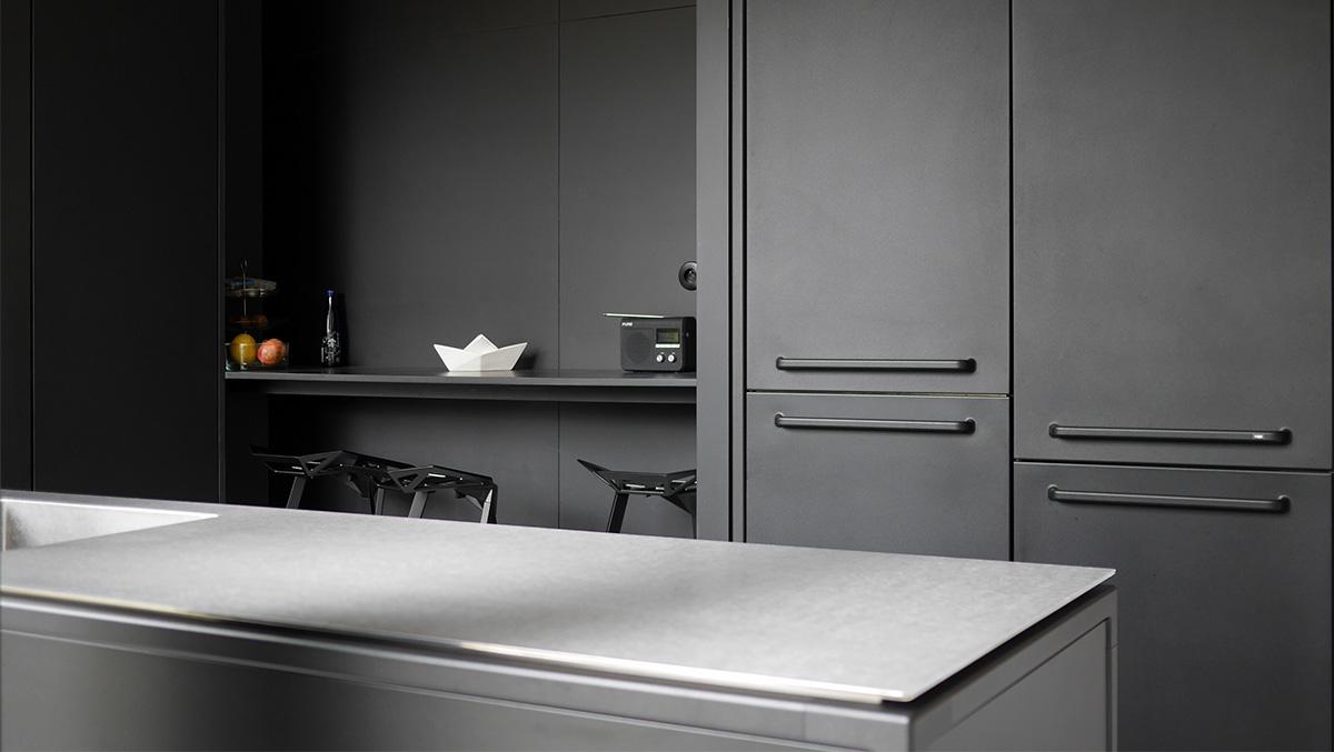 Extension contemporaine à Caluire et Cuire en ossature bois et bardage aluminium imitation zinc noir. Cuisine minimaliste noir et inox, scandinave de marque Vipp, détail poignées métal et plan de travail inox.