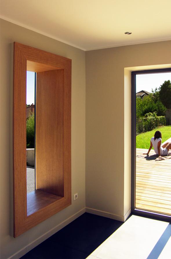 Extension contemporaine à Caliure et Cuire en ossature bois et parement ciment Viroc. Chambre avec une fenêtre caisson.