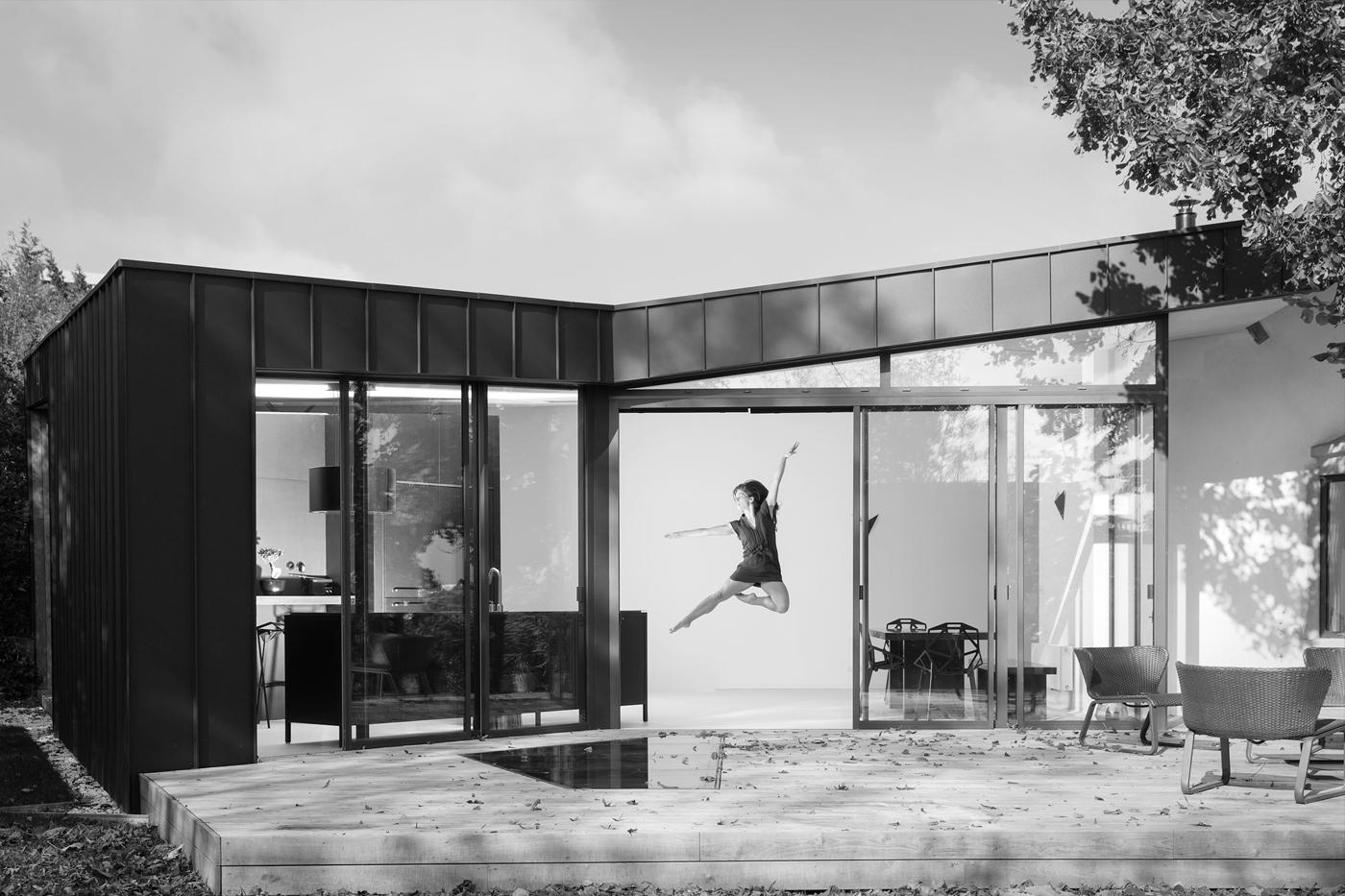 Extension contemporaine à Caluire et Cuire en ossature bois et bardage aluminium imitation zinc noir. Façade triangle, terrasse mélèze.