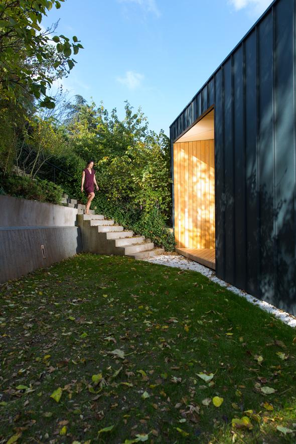 Extension contemporaine à Caluire et Cuire en ossature bois et bardage aluminium imitation zinc noir. Façade triangle, terrasse mélèze. Entrée depuis l'escalier dessiné comme une alcove en bois dans la facade en imitation zinc à joint debout. L'entre deux est traité en gravier blanc dans un style japonais.