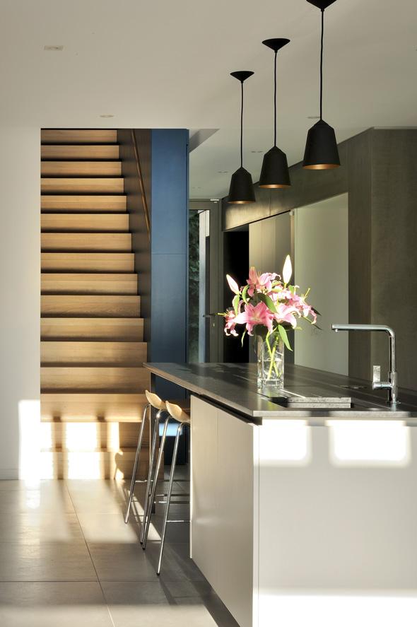Maison contemporaine dans l'ouest de Lyon. Cuisine avec un ilot, suspensions et escalier bois.