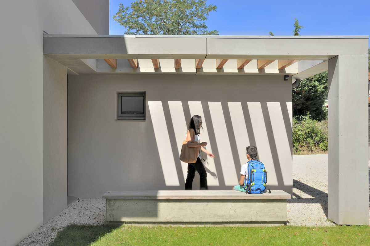 Maison contemporaine dans l'ouest de Lyon. Entrée avec une pergola et un banc en béton banché.