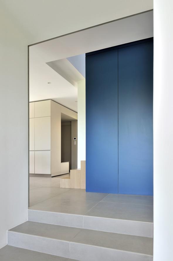Maison contemporaine dans l'ouest de Lyon. Meuble bleu avec rangements sur mesure et accès au salon par quelques marches.