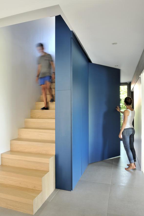 Maison contemporaine dans l'ouest de Lyon. Escalier en bois avec un meuble bleu canard sur mesure permettant de refermer le bureau.
