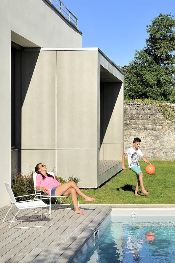 Maison contemporaine dans l'ouest de Lyon. Volume du salon qui ressort, piscine et jardin.