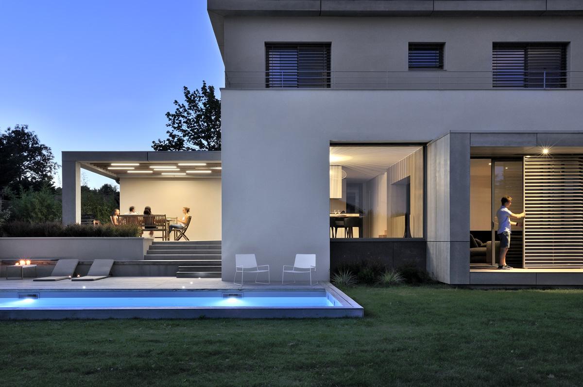 Maison contemporaine dans l'ouest de Lyon. Boite du salon avec éclairage, piscine et terrasse avec pergola.