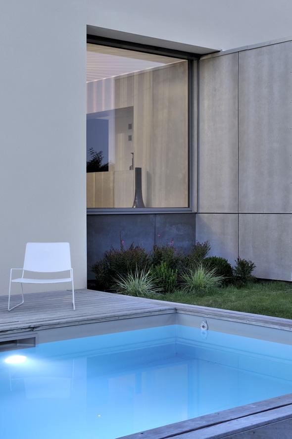Maison contemporaine dans l'ouest de Lyon. Salle à manger avec vitrage fixe sur la piscine, bardage du salon continue à l'intérieur.