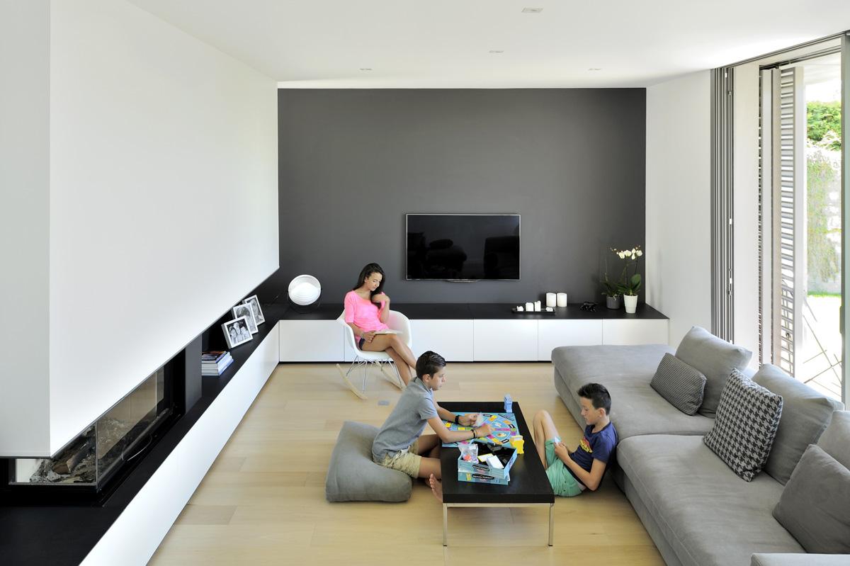 Maison contemporaine dans l'ouest de Lyon. Salon avec cheminée intégrée et meuble tv en agencement sur mesure.