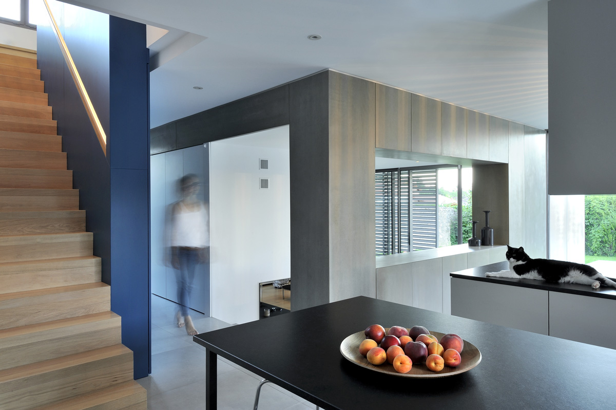 Maison contemporaine dans l'ouest de Lyon. Boite du salon en Viroc, escalier en bois et meuble sur mesure bleu.