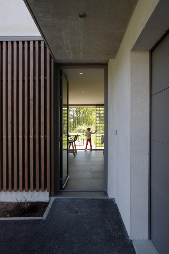 Maison contemporaine en Savoie avec un bardage bois et un abri-voiture en béton brute. Vue depuis l'entrée traversante avec les baies vitrées du salon.