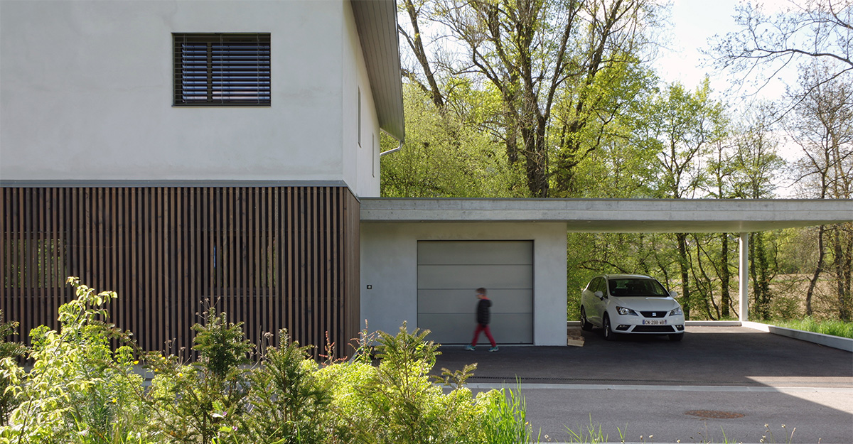 Maison contemporaine en Savoie avec un bardage bois et un abri-voiture en béton brute. Vue depuis l'entrée.