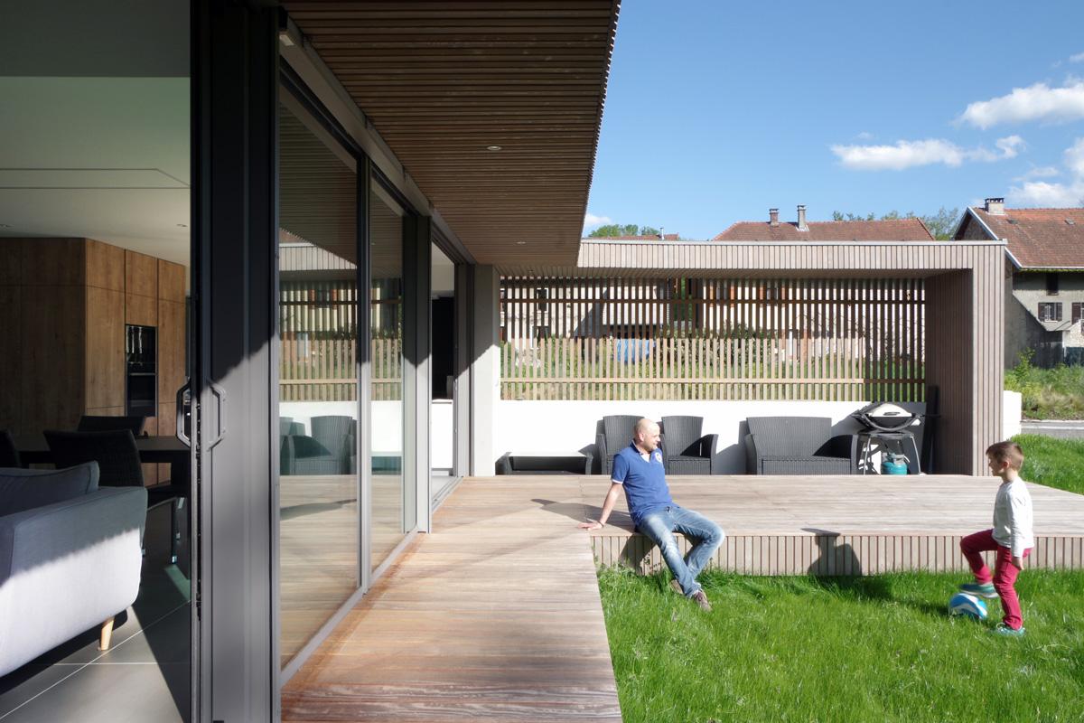 Maison contemporaine en Savoie avec un bardage bois et du béton brute. Terrasse bois et cuisine extérieure, porte fenêtre sur le jardin.