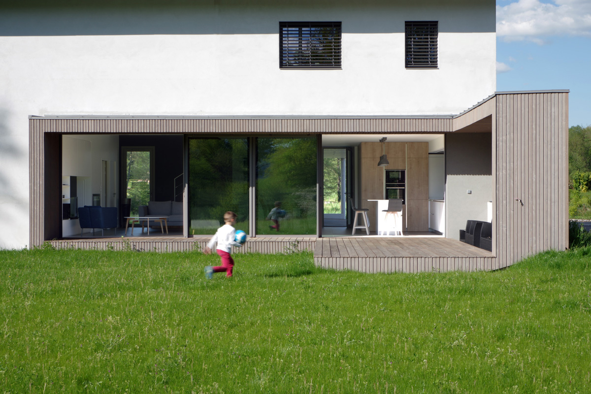 Maison contemporaine en Savoie avec un bardage bois et du béton brute. Terrasse et claustrât sur rue en bois.