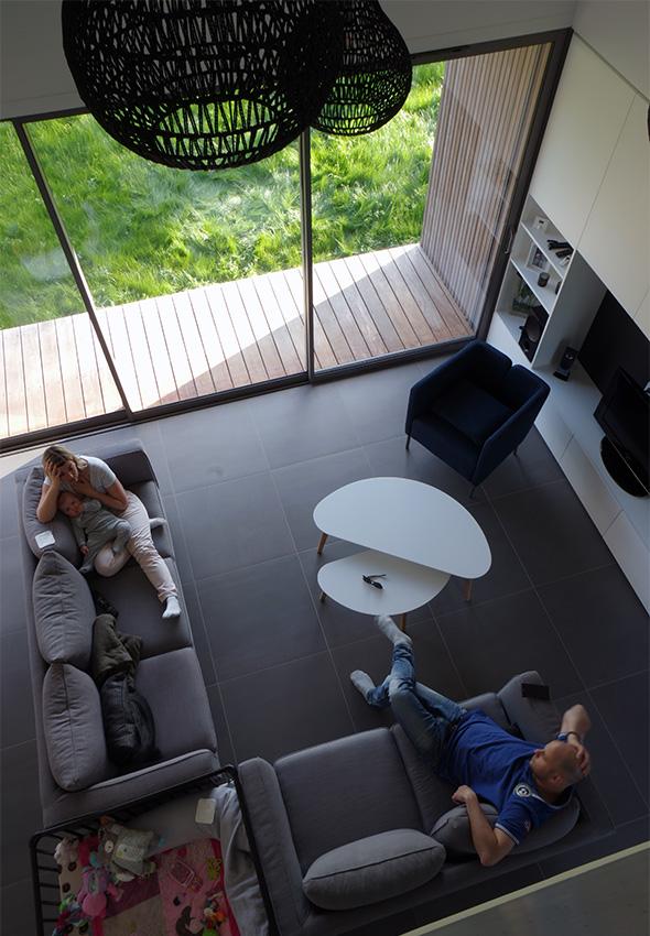 Maison contemporaine en Savoie avec un bardage bois et du béton brute. Salon double hauteur scandinave avec suspensions et table basse.