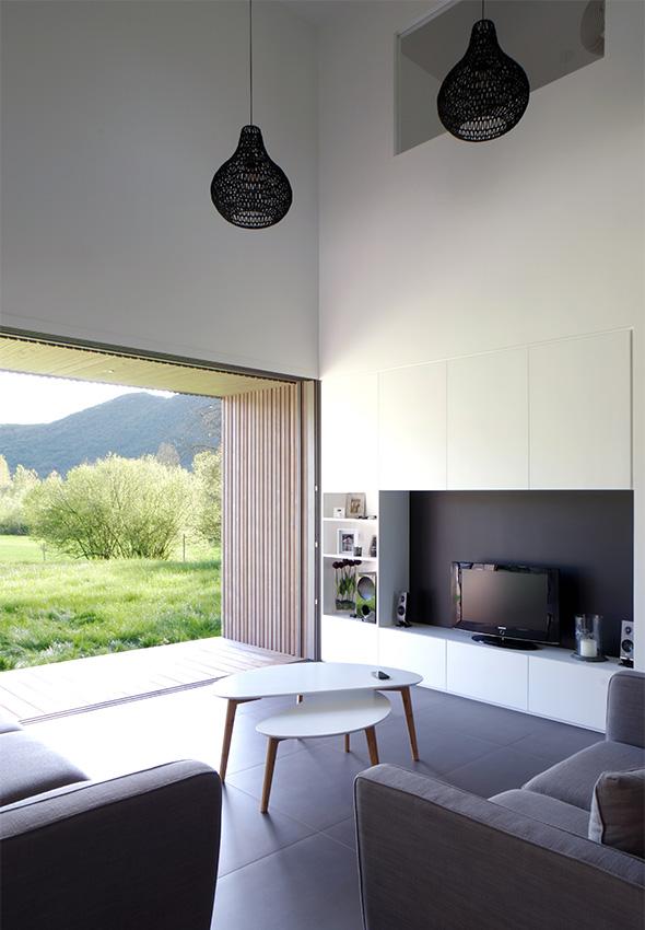 Maison contemporaine en Savoie avec un bardage bois et du béton brute. Salon double hauteur minimaliste avec terrasse sur le jardin.