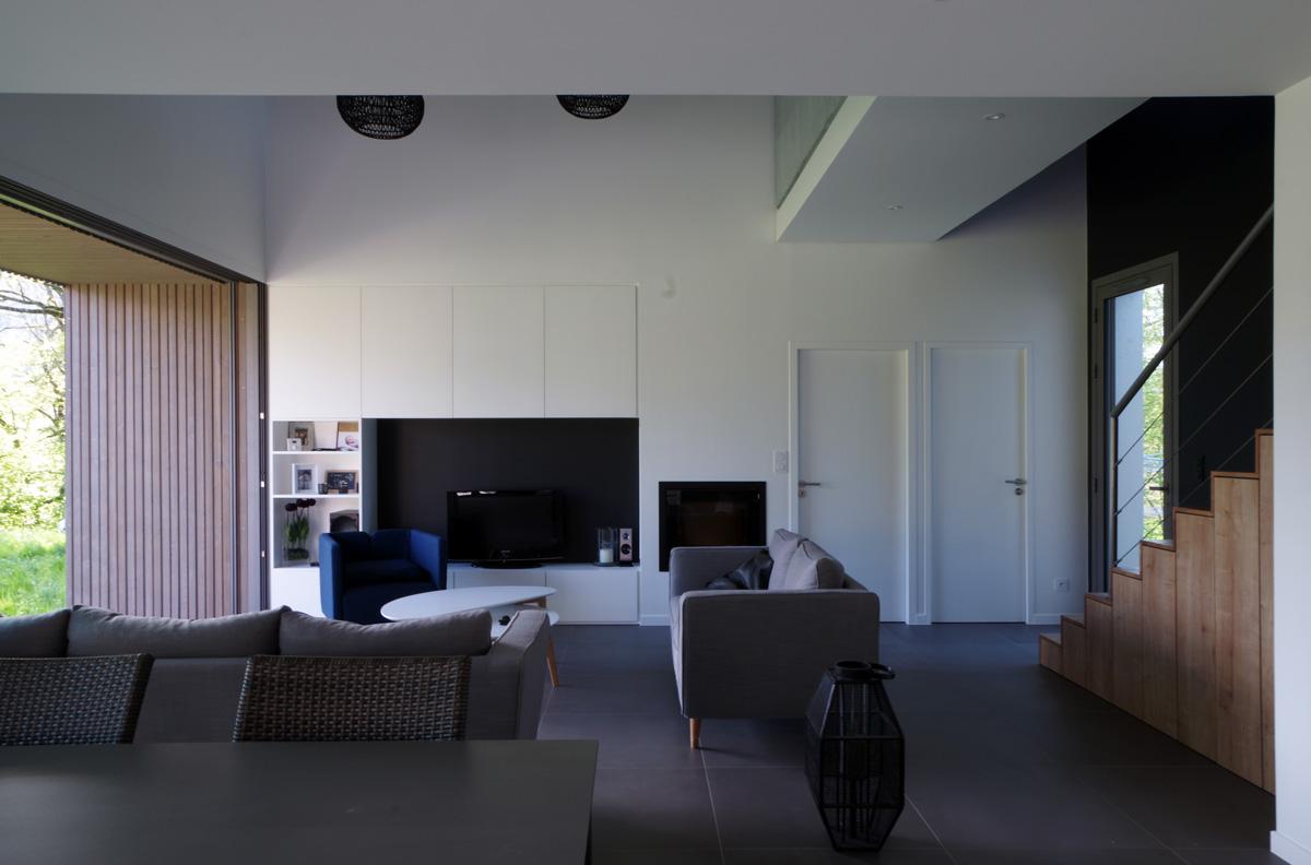 Maison contemporaine en Savoie avec un bardage bois et du béton brute. Salon double hauteur meuble tv sur mesure.