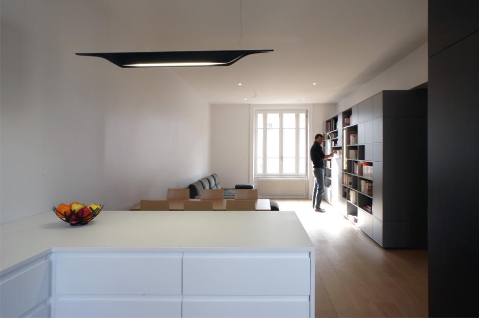 Rénovation d'un appartement contemporain à Lyon avec un meuble central sur mesure. Cuisine avec îlot et bibliothèque dans le salon.