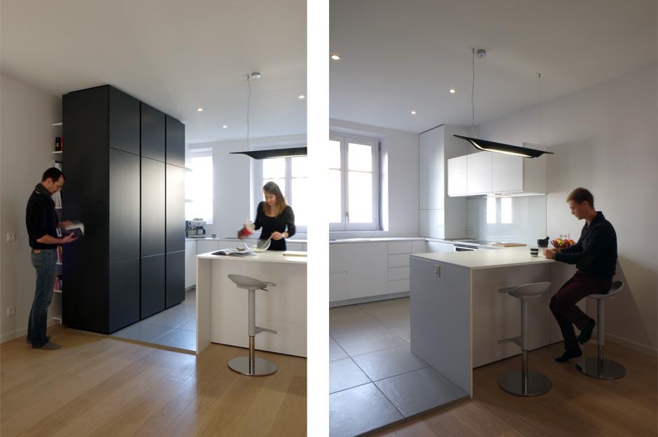 Rénovation d'un appartement contemporain à Lyon avec un meuble central sur mesure. Cuisine avec îlot et bar et rangements intégrés.