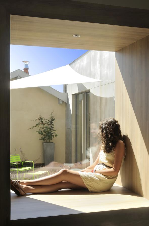Extension contemporaine à Caliure et Cuire en ossature bois et parement ciment Viroc. Fenêtre caisson bois servant d'assise, de banc.
