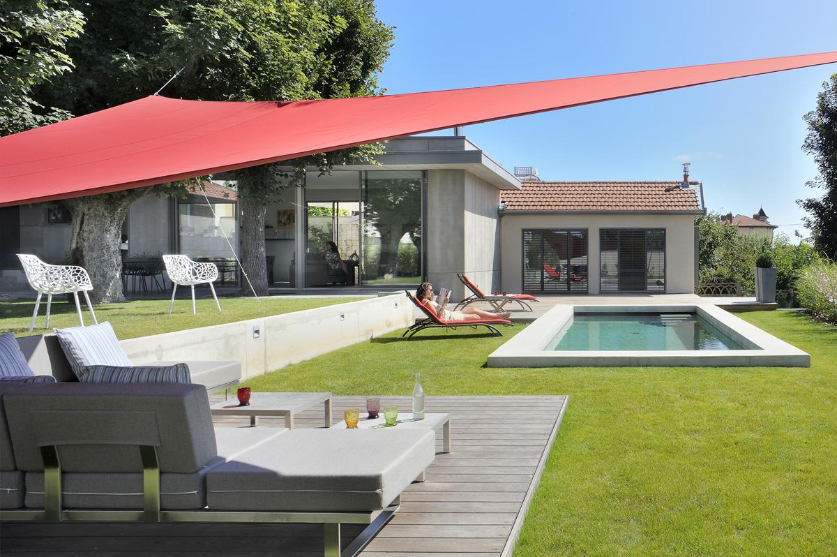 Extension contemporaine à Caliure et Cuire en ossature bois et parement ciment Viroc. Extérieur avec piscine béton et voile d'ombrage, pool house bois.