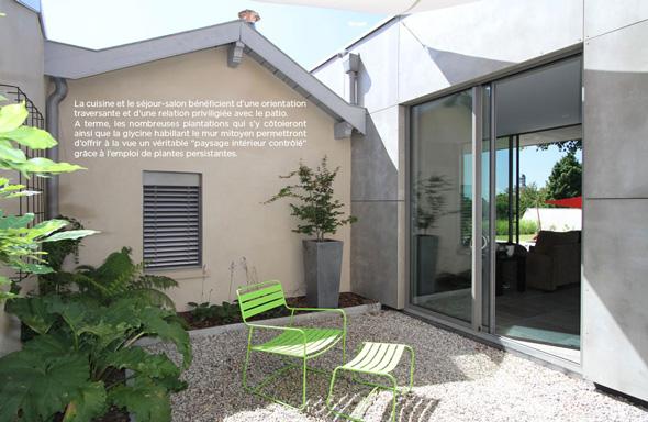 Extension contemporaine à Caliure et Cuire en ossature bois et parement ciment Viroc. Extérieur avec patio, bardage béton.