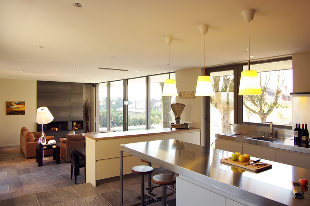 Extension contemporaine à Caliure et Cuire en ossature bois et parement ciment Viroc. Cuisine ilôt en intox et salon ouvert sur le jardin.