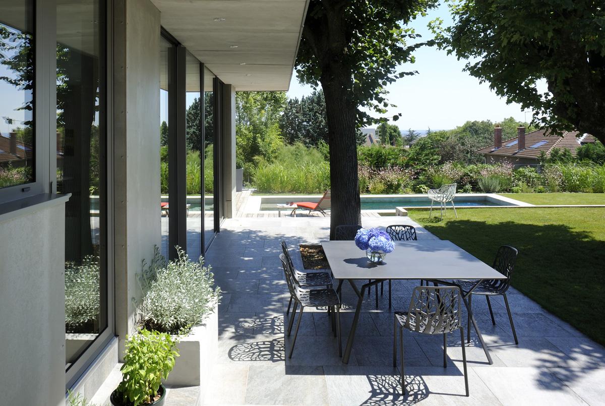 Extension contemporaine à Caliure et Cuire en ossature bois et parement ciment Viroc. Terrasse en prolongation du salon, avec casquette béton.