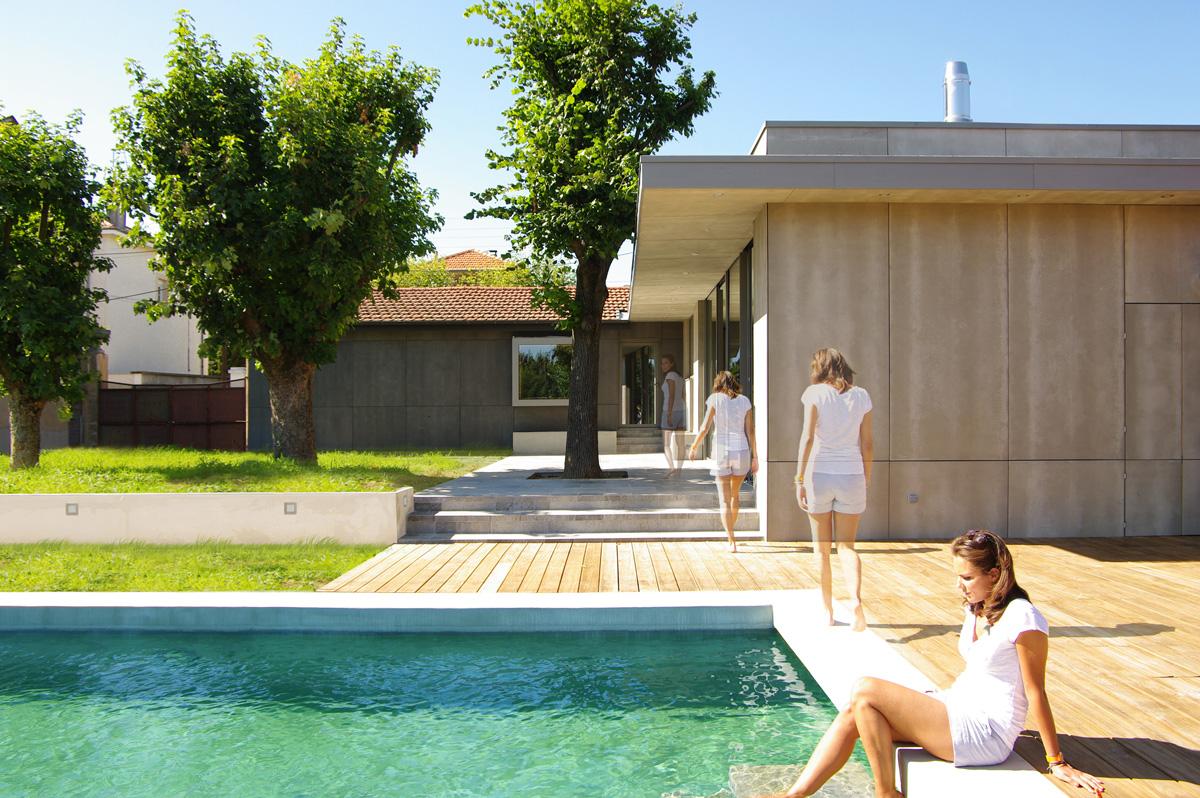 Extension contemporaine à Caliure et Cuire en ossature bois et parement ciment Viroc. Terrasse bois et piscine béton brute et marche encastrée, façades béton viroc.