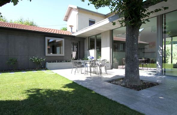 Extension contemporaine à Caliure et Cuire en ossature bois et parement ciment Viroc. Terrasse et salon dans le prolongement grâce à de larges baies coulissantes.